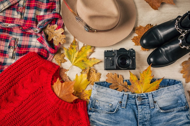 Lay piatto di stile donna e accessori, maglione lavorato a maglia rosso, camicia a scacchi, jeans in denim, stivali in pelle nera, cappello, tendenza moda autunnale, vista dall'alto, vestiti, foglie gialle Foto Gratuite