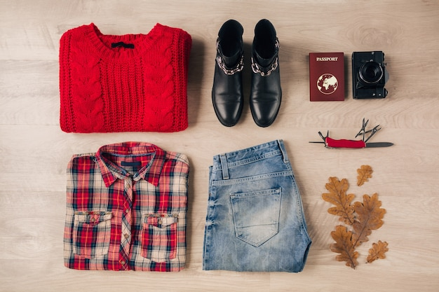 Flat lay of woman style and accessories, red knitted sweater, checkered shirt, jeans, black leather boots, autumn fashion trend, vintage photo camera, swiss knife, passport, traveler outfit Free Photo