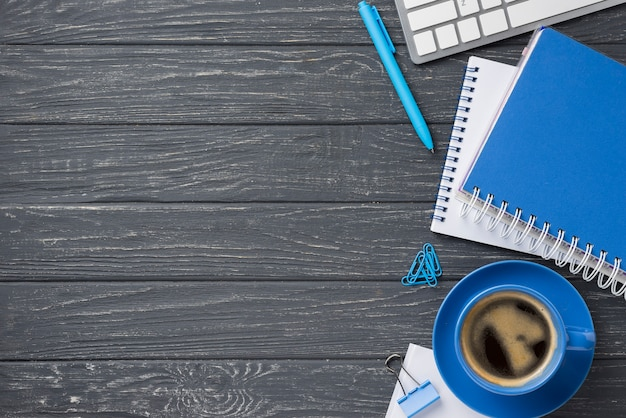 Flat lay of wooden desk with notebooks and coffee cup with copy space Free Photo