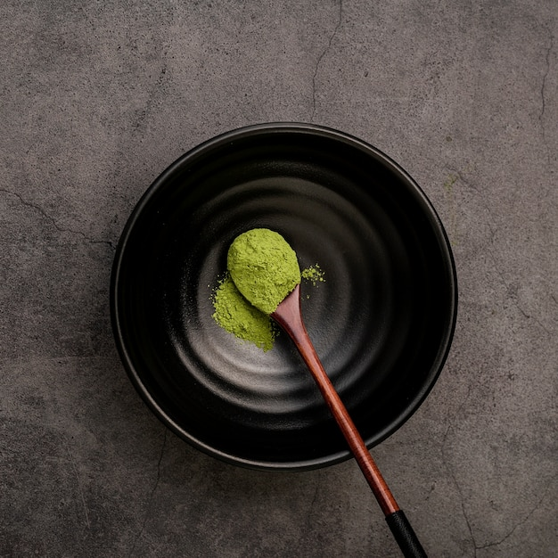 Flat lay of wooden spoon in bowl with matcha tea powder Free Photo