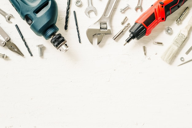Flat lay of working construction tools on grunge white wood. Premium Photo