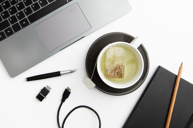 お茶のカップとフラットレイアウト作業プレート 無料写真