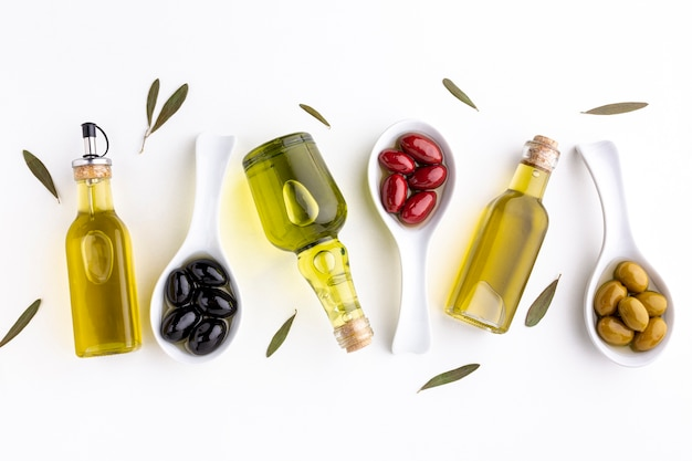 Flat lay yellow red black olives in spoons  with leaves and oil bottles Premium Photo