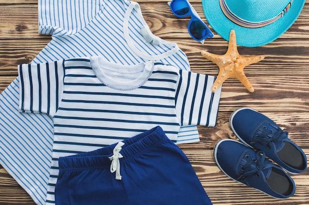 子供服のフラットはまだ。子供のワードローブ。小さな男の子のためのビーチと休暇の服。木製の背景 Premium写真