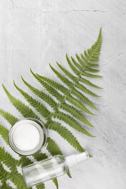 Flat view of a cream box and bottle on a leaf and marble background Free Photo