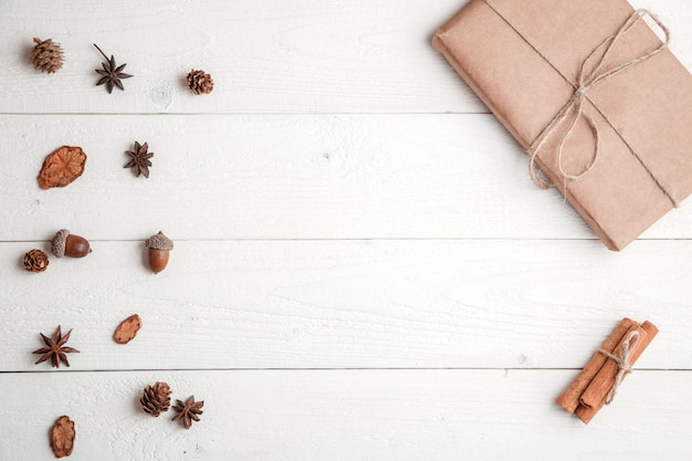 . flatlay. cinnamon,spruce branches and christmas gift on white wooden background Premium Photo