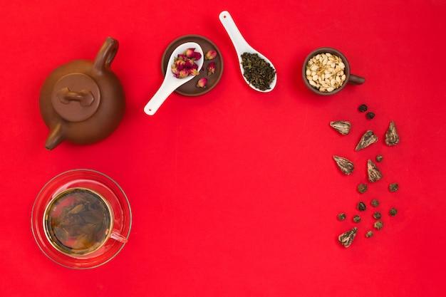 Плоская рамная композиция с китайскими листьями зеленого чая, бутонами роз, цветами жасмина и глиняным чайником. красный фон Premium Фотографии