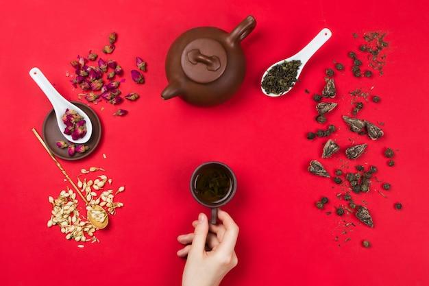 Плоская рамная композиция с китайскими листьями зеленого чая, бутонами роз, цветами жасмина, чайником и женскими руками, держащими чайную чашку. красный фон Premium Фотографии
