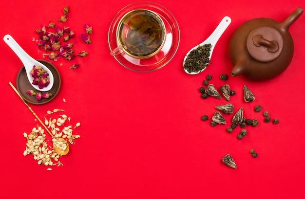 Плоская композиция из китайского зеленого чая, розовых бутонов, цветов жасмина и сухих чайных листьев. красный фон copyspace Premium Фотографии