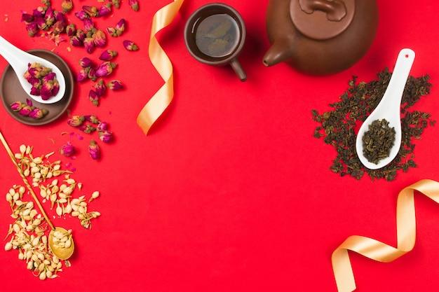 Плоская рамная композиция с китайским зеленым чаем, бутонами роз, цветами жасмина и золотыми лентами. красный фон copyspace Premium Фотографии