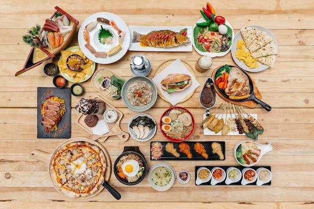 Flatlay of international foods on wooden table. Premium Photo