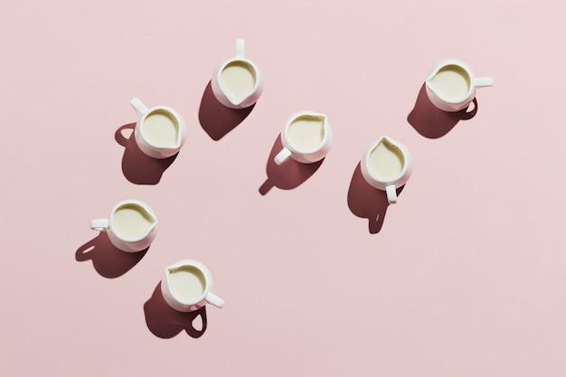 Flatlay белых сливок с овсяным молоком на пастельно-розовом фоне Premium Фотографии