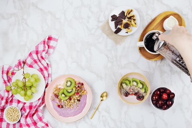 Flatlay of vegan breakfast with plant based yogurt bowls topped with kiwi slices, granola, chia seeds, smoothie bottle and coffee with soy milk on marble background Premium Photo