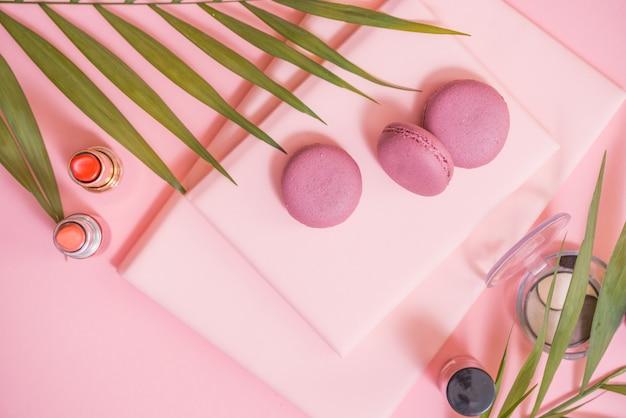 ピンクのテーブルにノート、ケーキマカロン、花のflatlay。マカロンと美しい朝食 Premium写真
