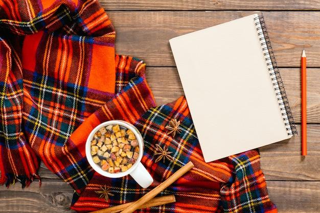 Flatlay秋の組成物。赤い女性ファッションスカーフ、ヴィンテージ紙メモ帳、ティーカップ、ペン、シナモンスティック Premium写真