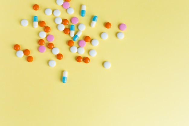 Различные различные таблетки, таблетки на желтом фоне. многие таблетки и таблетки с пространством для текста. здравоохранение. вид сверху. копировать пространство фармацевтическая картина. flatlay. хороший фон Premium Фотографии