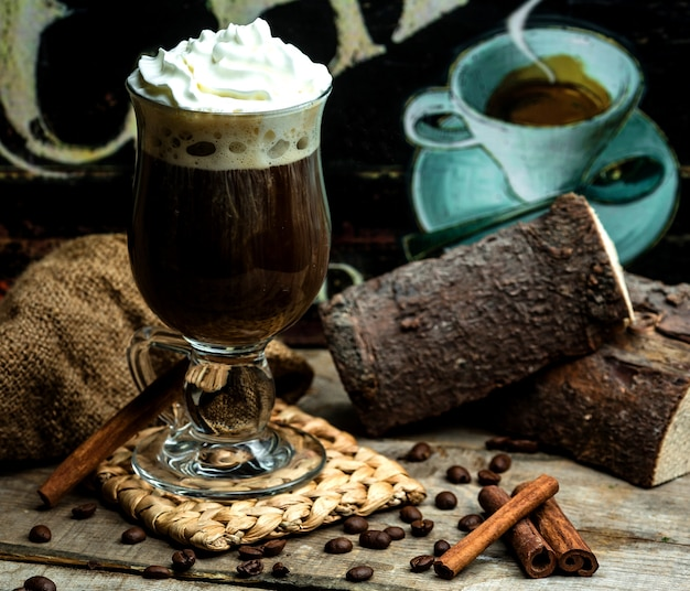 Flavored coffee with cinnamon and whipped cream Free Photo
