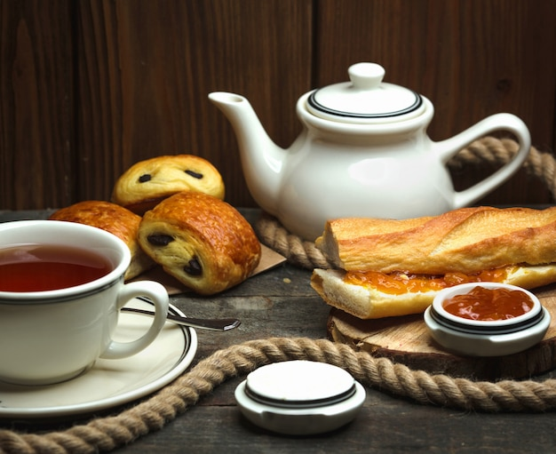 Flavored tea and a loaf of bread buttered with jam Free Photo