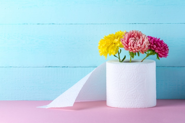 Flavored toilet paper roll and flowers on a pink table. toilet paper with a smell. hygiene concept. toilet paper concept. Premium Photo