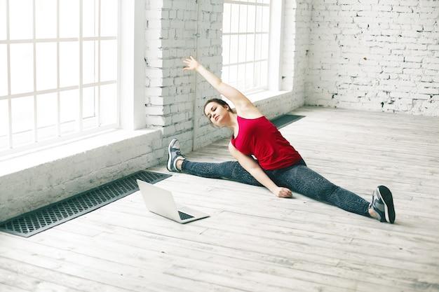柔軟性と強さ。ポータブルコンピューターでオンラインでヨガのチュートリアルを見ながら、自宅で完璧な体の筋肉を伸ばし、側脚を分割して右に曲げるゴージャスな若い女性 無料写真