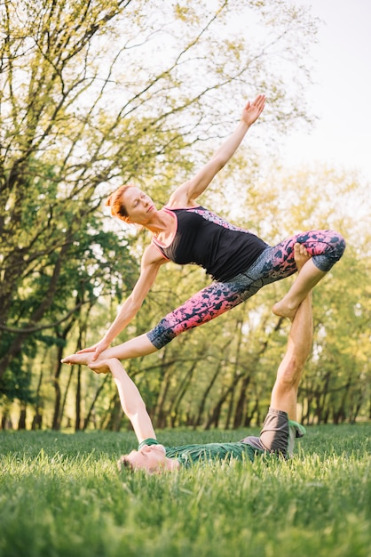 Flexible couple practicing acro yoga in park Free Photo
