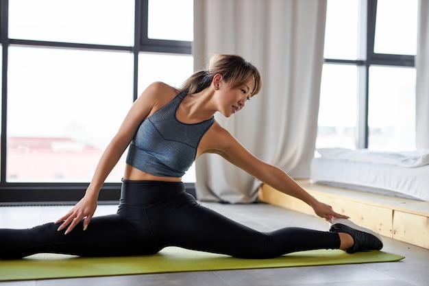 体を伸ばすスポーツ服を着た柔軟な女性は、自宅で一人でトレーニングを楽しんだり、検疫中に部屋でスポーツトレーニングをしたりします。ヨガマットの上で部屋で運動する Premium写真