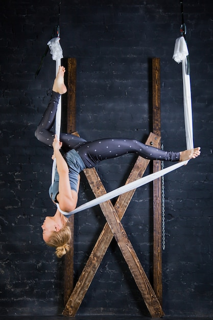 Гибкая посадка молодая спортивная женщина практикует воздушную йогу в гамаке Premium Фотографии