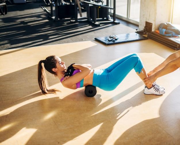 パーソナルトレーナーの助けを借りて、日当たりの良いジムで泡ローラーで運動を行う柔軟なスリムな若い女性。 Premium写真