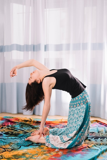 Flexible young woman doing yoga at gym Free Photo
