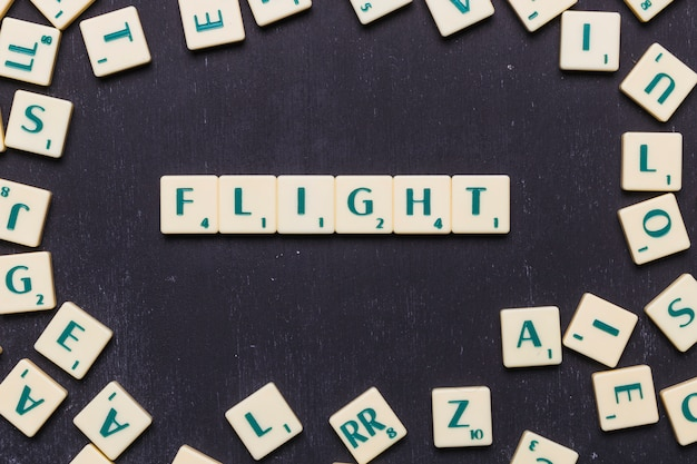 Flight word arranged on black background surrounded by scrabble letters Free Photo
