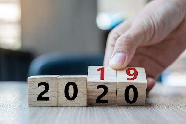 Flip over block 2019 to 2020 word on table background Premium Photo