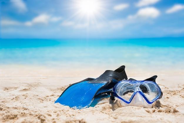Flipper and snorkel on sand beach with bright sun Premium Photo