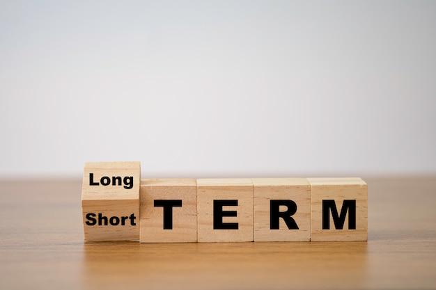 Переверните деревянный кубический блок для смены краткосрочной и долгосрочной перспективе. бизнес инвестиционная концепция. Premium Фотографии
