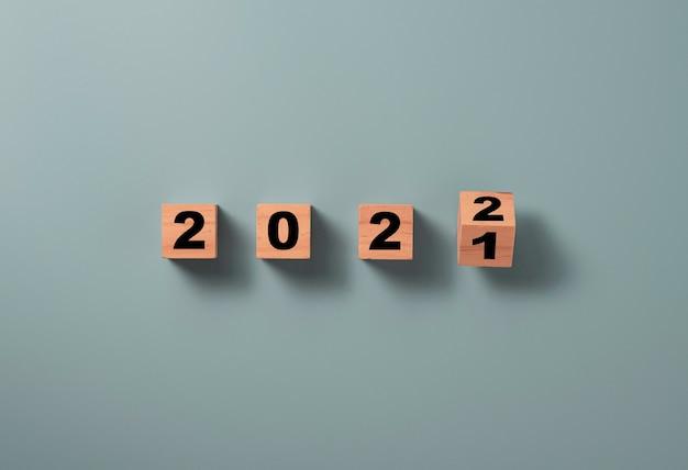 파란색 배경, 메리 크리스마스 및 새해 복 많이 받으세요 준비 개념에 2021에서 2022로 변경하려면 나무 블록 큐브를 뒤집습니다. 프리미엄 사진