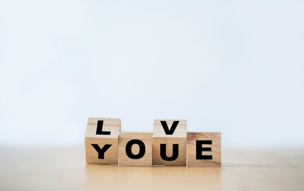 Flipping wooden block cube which print screen love you wording. valentines ' s day concept. Premium Photo