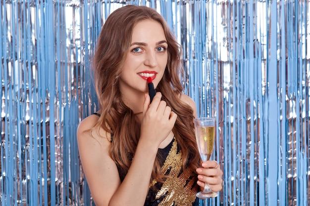 シャンパンでいちゃつく女性は唇に赤いポマードを適用し、直接カメラを見て、銀の見掛け倒しで青い壁に孤立したポーズ 無料写真
