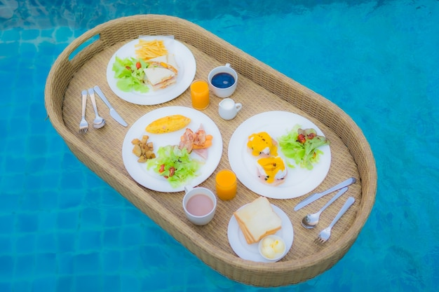 Floating breakfast around outdoor swimming pool Free Photo