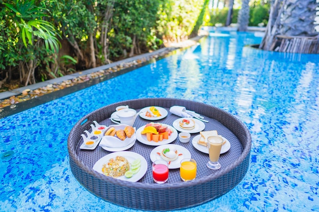 Floating breakfast set in tray with fried egg omelette sausage ham bread fruit milk juice coffee Free Photo