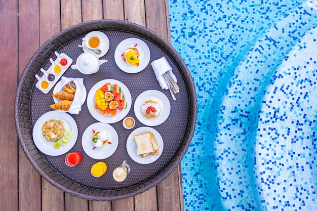 Floating breakfast tray around outdoor swimming pool with bread fruit egg coffee and juice Free Photo