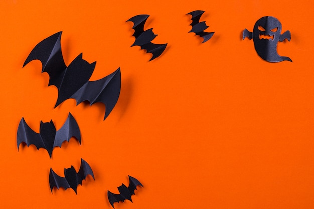 Flock of black paper bats and ghost on orange paper background. Premium Photo