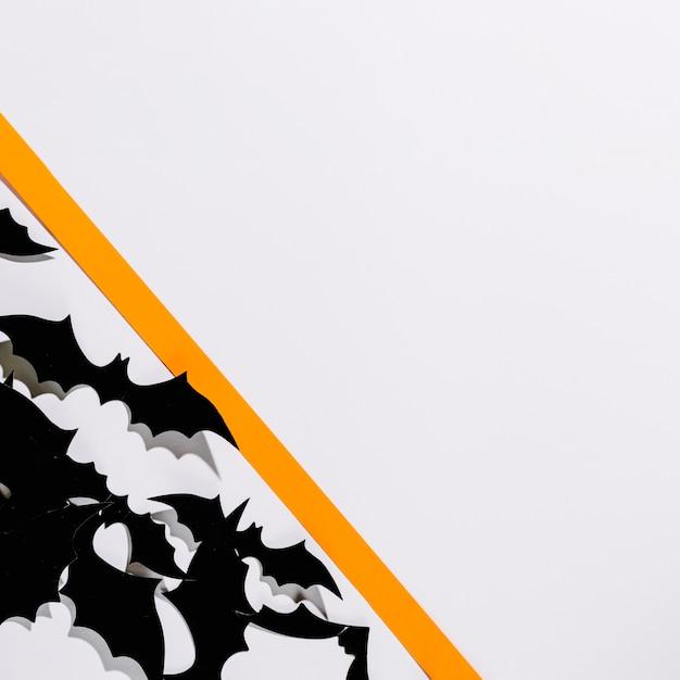 Flock of halloween bats laid behind paper stripe Free Photo