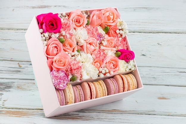 Цветочная композиция из розовых роз с макаронами разных цветов Premium Фотографии