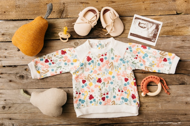 Floral baby clothing with shoes; pacifier; ultrasound picture and stuffed toy on wooden table Free Photo