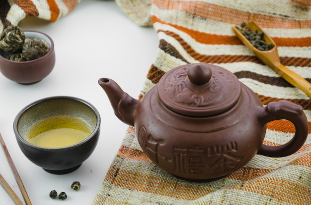 Floral blooming tea ball and oolong tea dust tea against white background Free Photo