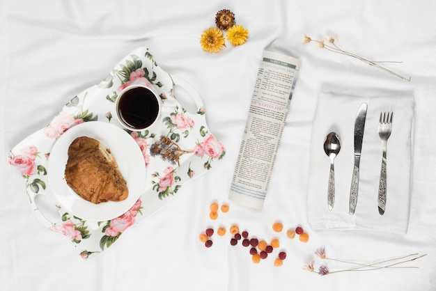 Floral breakfast tray; raspberry; rolled up newspaper; flower and cutlery on white napkin over the satin cloth Free Photo