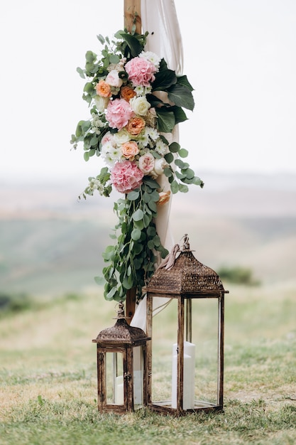 Floral composition made of eucalyptus and tender pink flowers with candles outdoors Free Photo