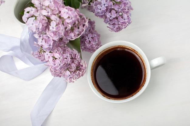 一杯のコーヒー、スタイリングされたストックイメージ、フラットレイ、上面図と白い木製の背景に美しい紫色のライラックで作られた花の組成物 Premium写真