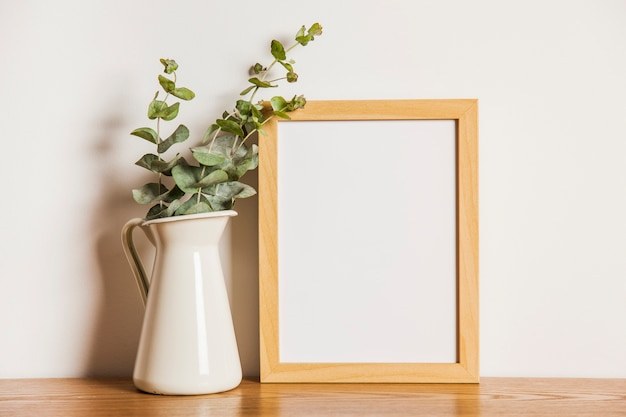 Floral composition with frame next to plant Free Photo