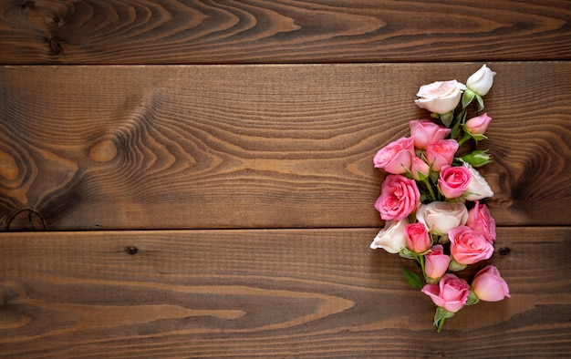 Floral composition with a wreath of pink roses on wooden background. valentine's day background. Premium Photo