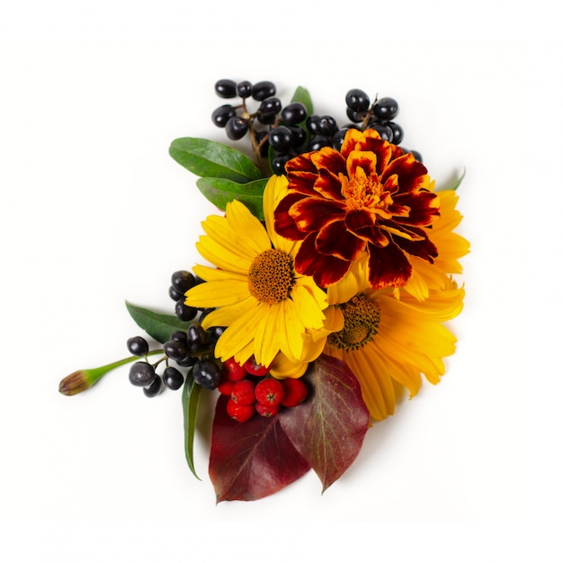 Floral composition of yellow daisies, red autumn leaves and berries. autumn composition on a white background. Premium Photo